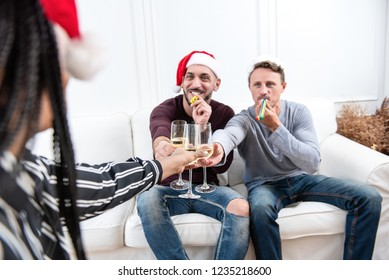 Gay couple drinking champagne celebrating Christmas at home with friends