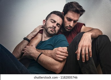 Gay couple going through rough times, comforting each other, experiencing quiet sadness