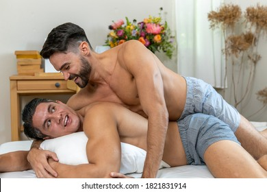 Gay couple having a good time on a bed. Gay in sleep short gives romantic hug to his partner in a bed room