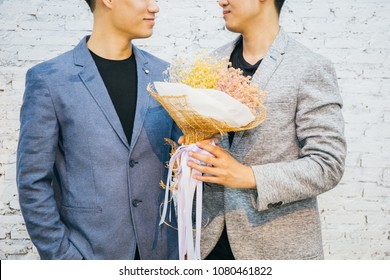Gay couple holding a bouquet of flowers, ready to give to his partner for special occasions or wedding proposal. Asian homosexual men together