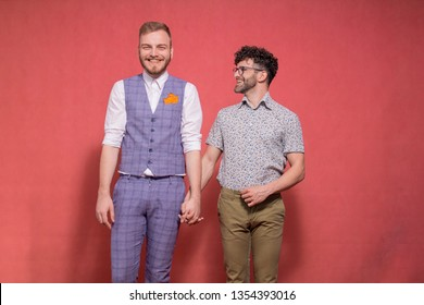 gay couple, holding hands together, posing in studio photo-shoot. one is looking to camera, while other one is looking to him.