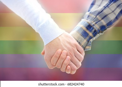 Gay couple holding hands together and LGBT flag on background