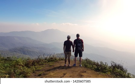 Gay couple holding hands at the top of the mountain (happy concept)