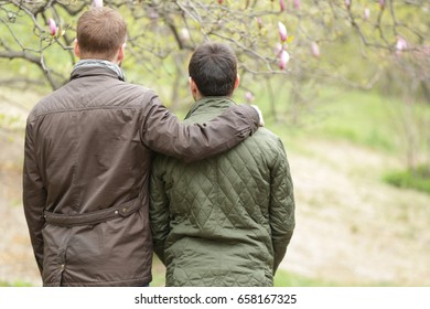 Gay couple hugging and walking in park