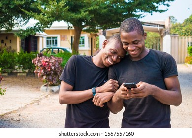 gay couple laughing together while using a phone together. two young black men walking and holding each other laughing together while viewing content on a mobile phone.