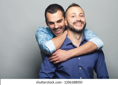 Gay couple love, Happy together concept. Two young men hugging each other and laughing over gray background. White shiny smiles. Close up. Copy-space. Studio shot