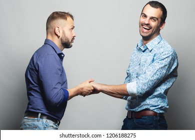 Gay couple love, Happy together, Proposal, Waiting for reply concept. Two young men holding their hands and laughing over gray background. White shiny smiles. Studio shot