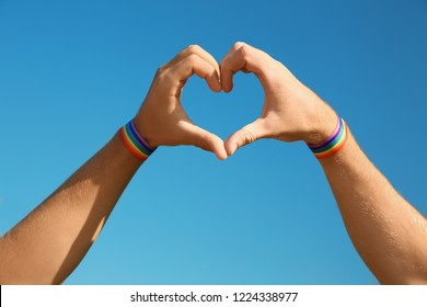 Gay couple making heart shape with their hands against blue sky, closeup