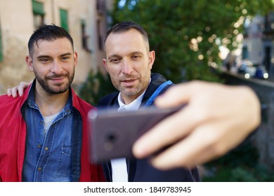 Gay couple making a selfie with their smartphone. Homosexual relationship concept.