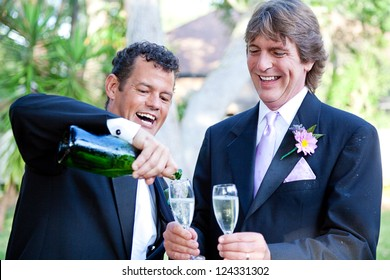 Gay couple pouring champagne to toast at their wedding.  The groom on the right is covered with champagne from the splash when the cork popped.