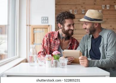Gay couple sat viewing menu in cafe