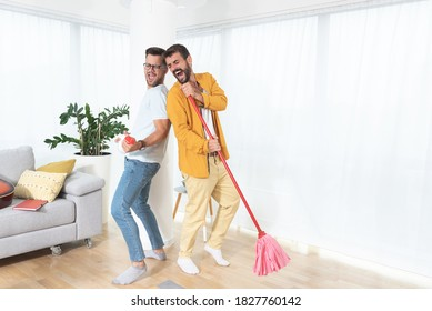 Gay couple singing while cleaning house