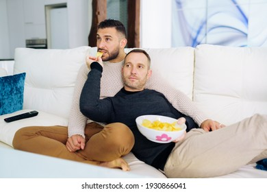 Gay couple sitting on the couch at home watching something on TV and having a snack. Homosexual relationship concept.