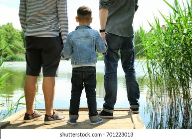 Gay couple with son on a pier