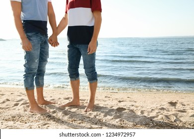 Gay couple standing barefoot on beach. Space for text