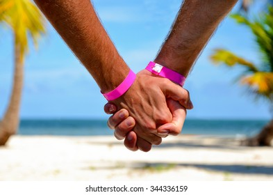 Gay couple travel close up holding hands watching on the beach