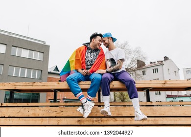 Gay couple turned into a rainbow flag sitting on a bench. Struggle for same-sex marriage
