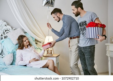 Gay couple waiting for their surrogate baby. The dads-to-be pampering the expectant mother, giving her presents and flowers. She's relaxing on the bed while taking gifts with a smile on her face.
