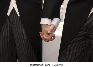 A gay couple walking back down the aisle after making their vows at their civil partnership.
