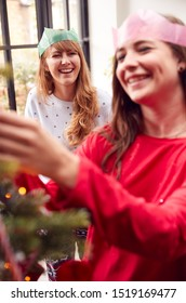 Gay Female Couple At Home Hanging Decorations On Christmas Tree Together