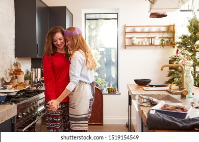 Gay Female Couple At Home In Kitchen Cooking Vegetarian Dinner On Christmas Day Together