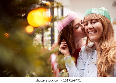 Gay Female Couple Kissing As They Hang Decorations On Christmas Tree At Home Together