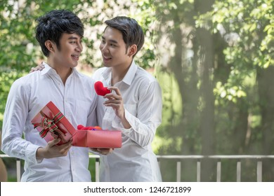 Gay homosexual couple holding two heart and gift box on valentines day.