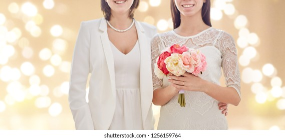 gay, homosexuality, same-sex marriage and lgbt concept - close up of happy married lesbian couple with flower bunch over festive lights background
