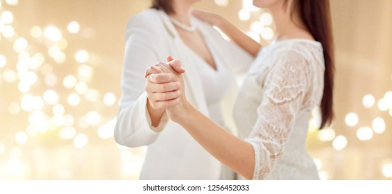gay, homosexuality, same-sex marriage and lgbt concept - close up of happy married lesbian couple dancing over festive lights background