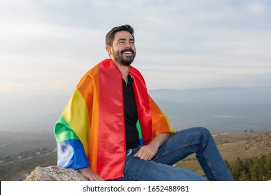 Gay laughing sitting with a gay flag .concept of gay, pride, diversity
