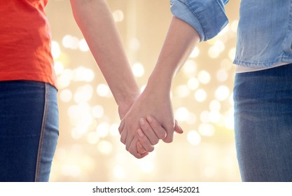 gay, lgbt and homosexuality concept - close up of happy lesbian couple holding hands over festive lights background