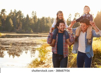 Gay Male Couple With Children Walking By Lake