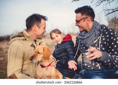 Gay male couple with daughter and small yellow dog enjoying outdoors at a picnic table