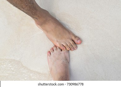 Gay male couple with feet together in sand and ocean on the beach on their honeymoon