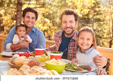 Gay Male Couple Having Outdoor Lunch With Daughters