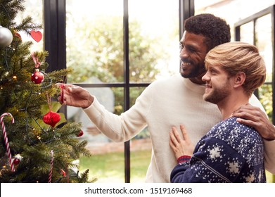 Gay Male Couple At Home Hanging Decorations On Christmas Tree Together