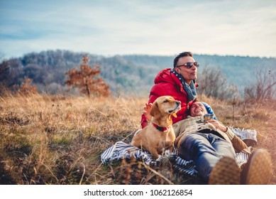 Gay male couple laying on blanket in grass outdoors and drinking coffee