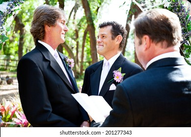 Gay male couple saying their marriage vows before a minister in lovely outdoor setting.