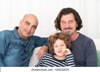 Gay men posing sitting on the sofa with their son