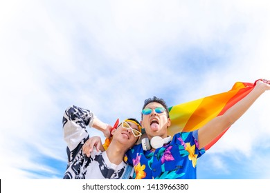 gay millennial men couple walking and smiling with pride flag. lgbt concept and gender equality among young people