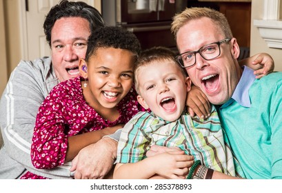 Gay parents pose with their children in the living room