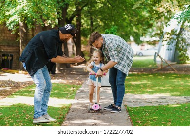 Gay parents teaching their daughter to ride a scooter. Young family spending joyful time in the park. LGBT parenting concept.