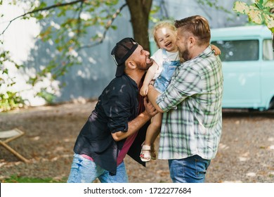 Gay parents with their daughter in the park. Cute moments of a family life.