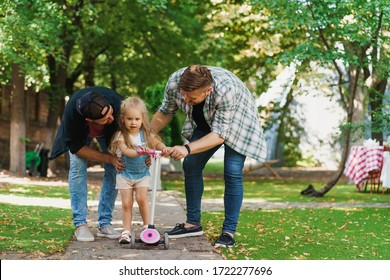Gay parents and their daughter in the park. Careful dads helping the child to ride a scooter for the first time.