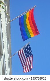 A gay pride and American flag against a blue sky
