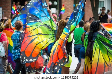 Gay pride carnival parade participants wearing colorful rainbow butterfly wing costumes in Greenwich Village