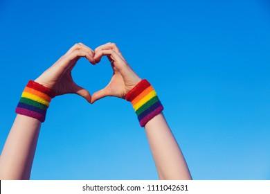 Il concetto di orgoglio gay. Braccialetto a forma di cuore con simbolo gay pride LGBT, bandiera arcobaleno
