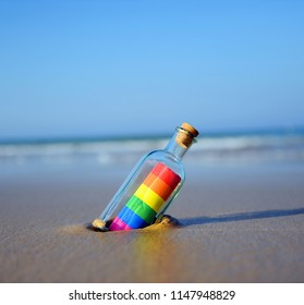 Gay pride message in a bottle on the seashore
