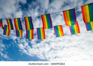 Gay pride rainbow flag bunting fluttering backlit by the sun against blue sky copy space