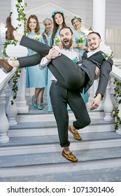 Gay wedding. Two grooms frolicking and laughing, while one carrying the other down the front porch steps. Female guests clad in similar blue dresses smiling in the background, tulips in their hands.